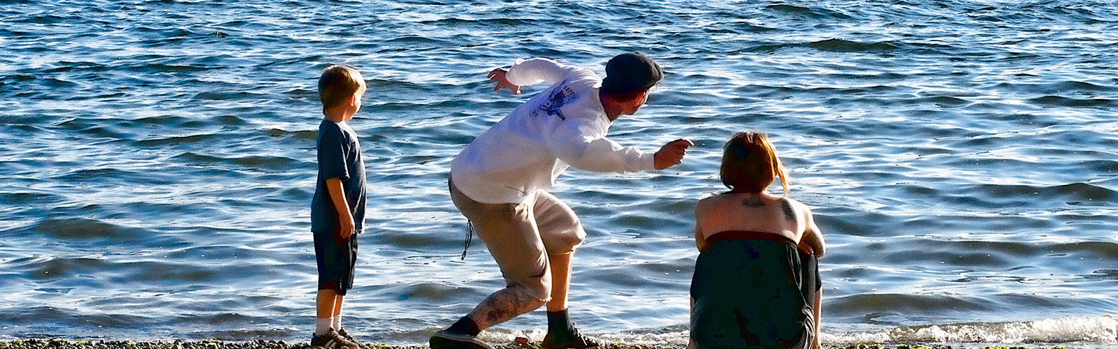 Man skipping a rock across the water with son and wife watching