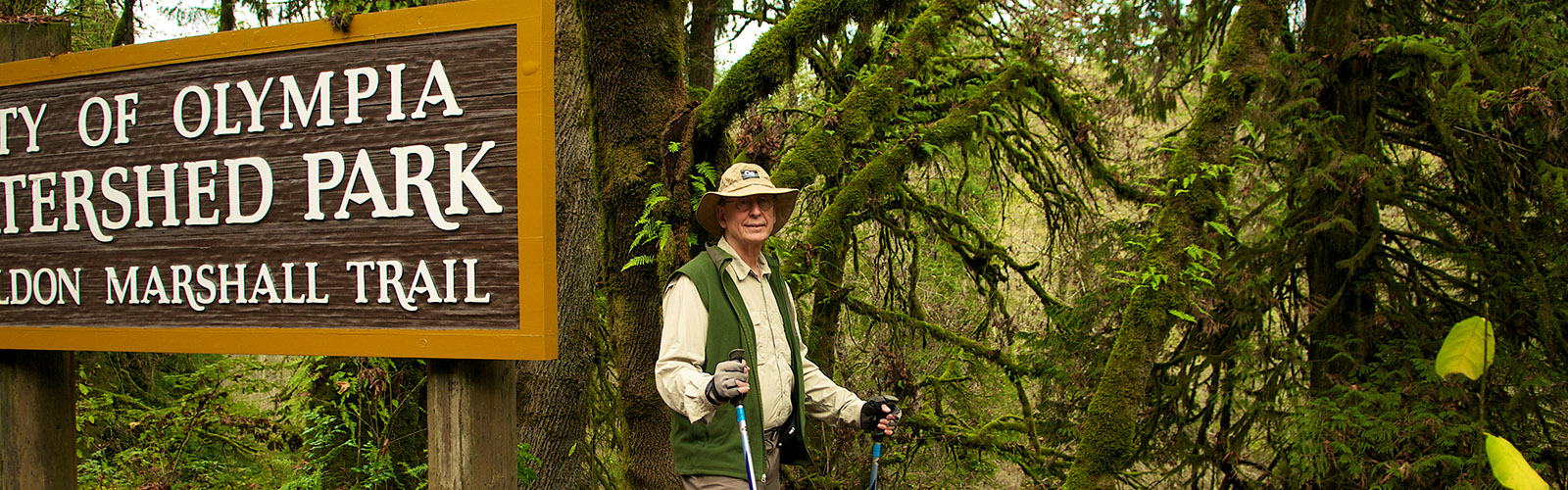 Male hiker standing at entrance of City of Olympia Watershed Park Don Marshall Trai