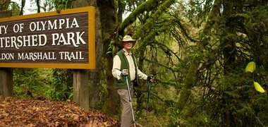 Male hiker standing at entrance of City of Olympia Watershed Park Don Marshall Trail