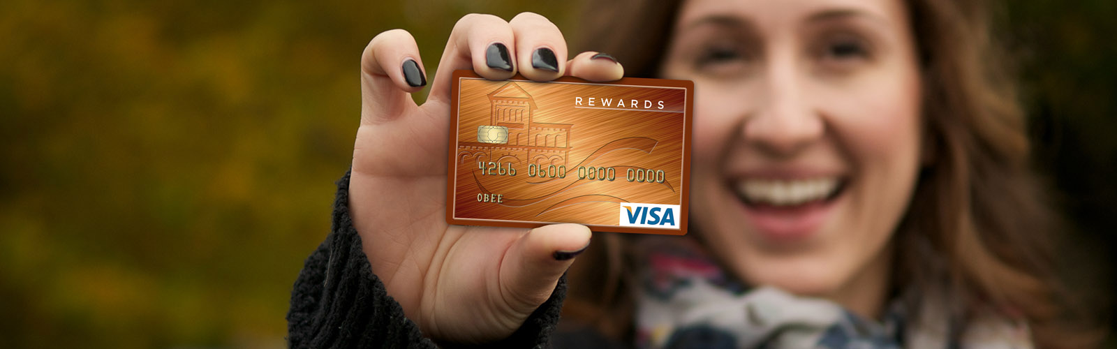 Picture of Smiling woman holding an O BEE Visa Platinum Card