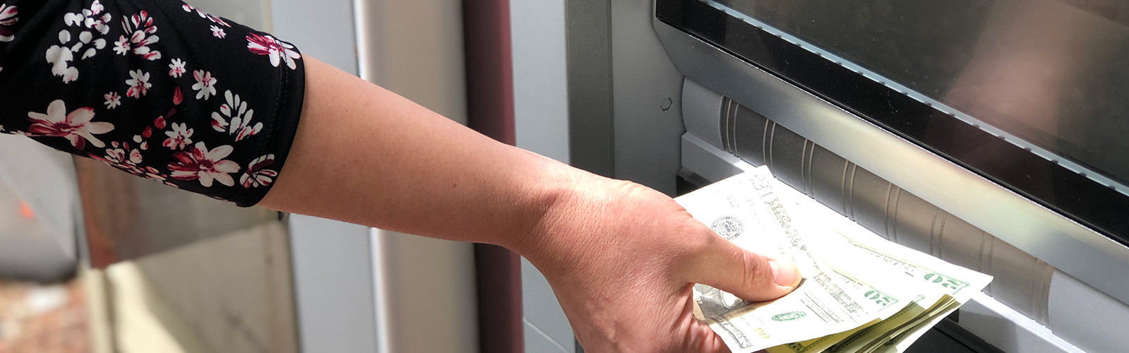 Woman putting money into ATM